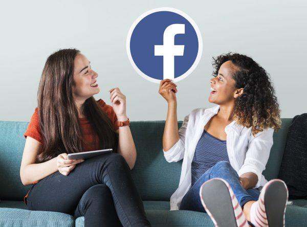 jeunes femmes tenant un icone facebook